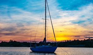 夕阳下海港停泊的帆船摄影图片