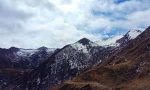 白云下的雪山美景摄影图片