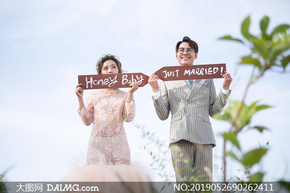 双手拿着牌子的美女帅哥婚纱照原片