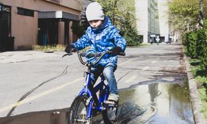 骑车通过积水区的小孩摄影 澳门线上必赢赌场