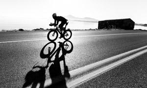 海边公路上的骑行人物剪影高清图片