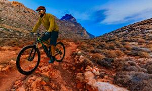 藍天云彩山地環境騎行人物高清圖片