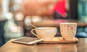 手机与两杯热咖啡特写摄影高清图片