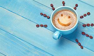 咖啡杯与摆成图案的咖啡豆高清图片