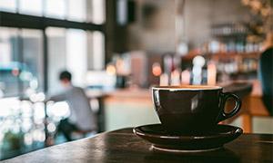 桌上黑色的咖啡杯特写摄影高清图片