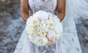 白色婚纱礼服新娘手中的玫瑰花图片