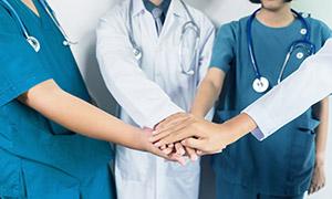 把手叠在一起加油的医生们摄影图片