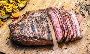 菜板上切成片状的烤肉摄影高清图片