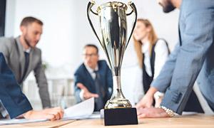 商务人物与桌上的奖杯摄影高清图片