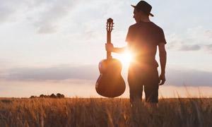 站在农田里拿着吉他的人物高清图片
