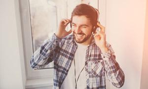戴耳機聽歌的格紋襯衫男子高清圖片