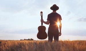 拿一把吉他的人物背影摄影高清图片