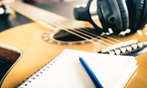 吉他上的活頁本與耳機攝影高清圖片