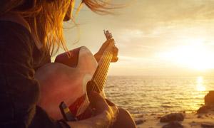夕陽下海邊彈琴的人物攝影高清圖片