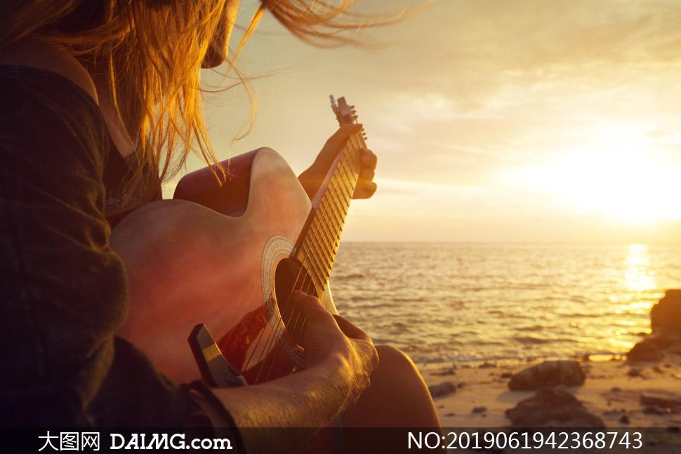 夕阳下海边弹琴的人物摄影高清图片