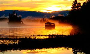 夕阳下的湖中船舶摄影图片