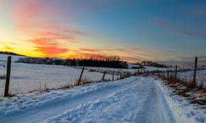 夕阳下的田园风光雪景摄影图片