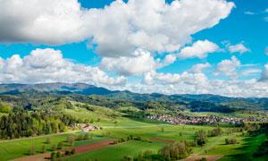山脚下美丽的村庄全景摄影图片