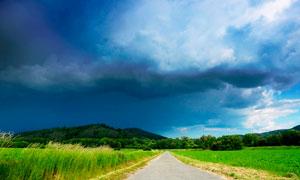 乌云下的田园道路和农田摄影图片