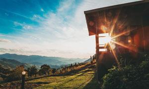 清晨山坡上的小屋攝影圖片
