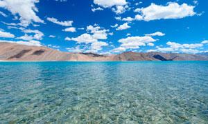 藍天下的海邊淺灘攝影圖片