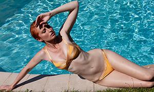 在泳池边晒阳光的泳装美女摄影原片