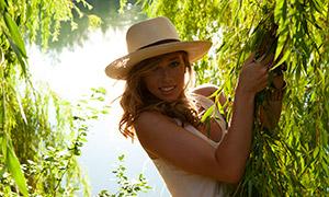 手抓着绿树枝叶的长发美女摄影原片