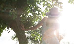 扶树而站立的长发美女摄影原片素材