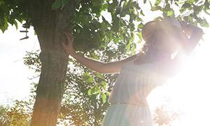 单手扶着树的白裙美女摄影原片素材