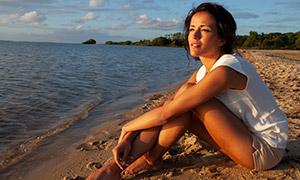 黄昏时在欣赏着海景的美女摄影原片