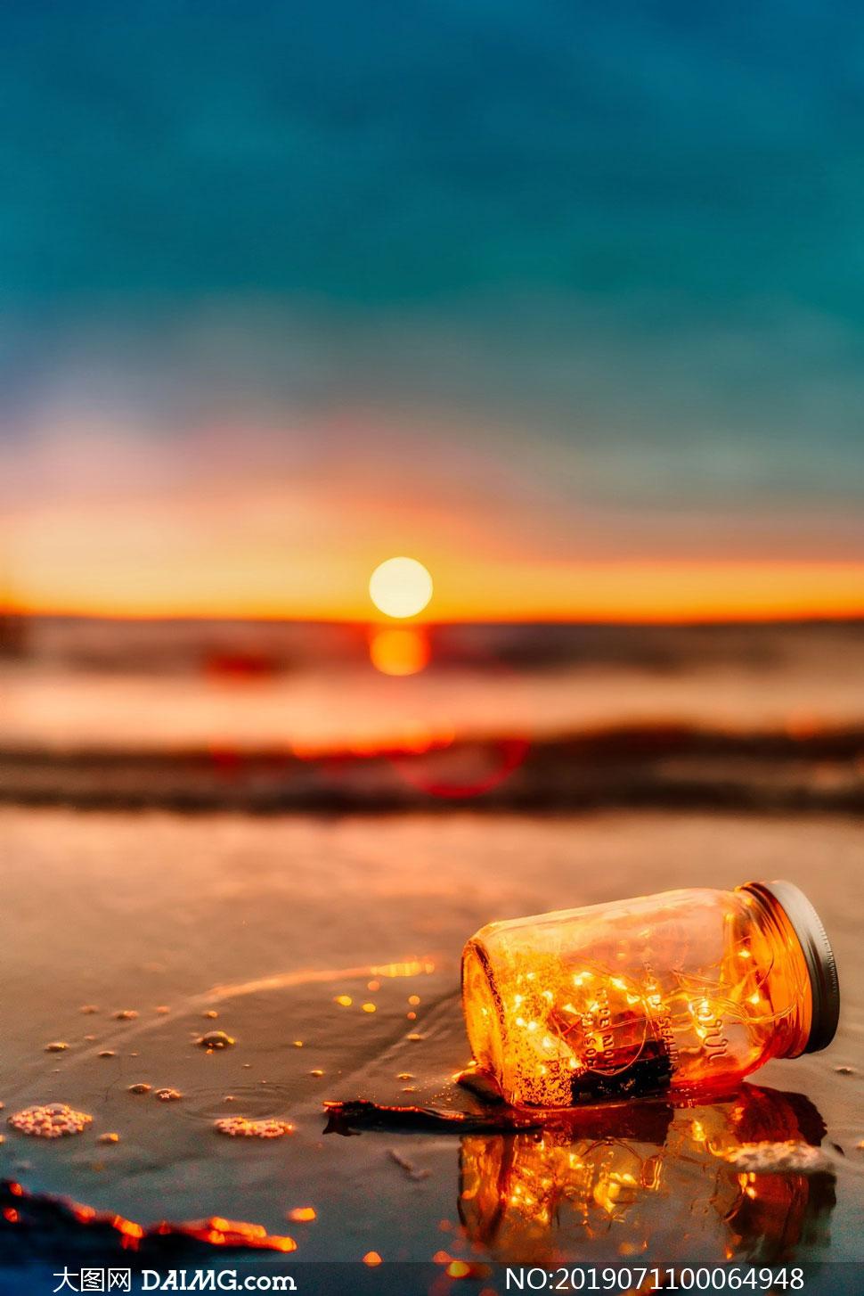黄昏下沙滩上美丽的漂流瓶摄影图片
