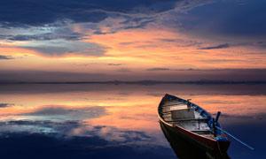 黄昏下在湖中停泊的小舟摄影图片
