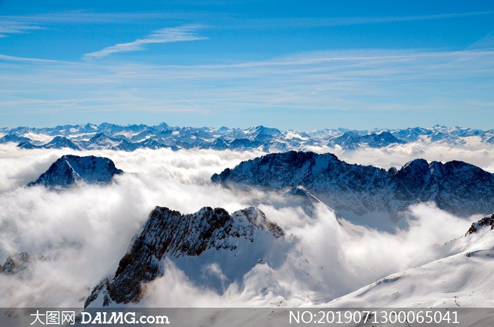 蓝天下连绵的雪山和云雾摄影图片