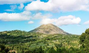 蓝天白云下的绿色火山摄影图片