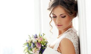 靠着墙手拿捧花的新娘摄影高清图片