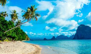 蓝天下的海滩和山峰摄影图片