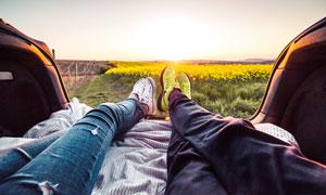 夕阳下在车里伸出双腿的情侣摄影图片