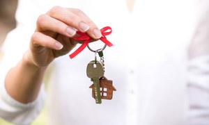 手中的鑰匙與房子模型掛件高清圖片