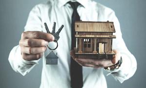 手中的钥匙与房屋模型特写高清图片