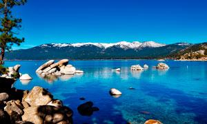 蓝天下湖泊中的岩石景观摄影图片