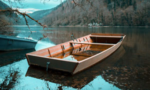 山间在湖泊中停泊的小舟摄影图片