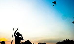 夕阳下放风筝的人物剪影摄影图片