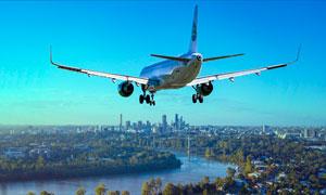 城市上空飞行的客机高清摄影图片