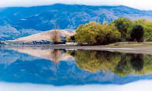 山脚下的树木和湖泊倒影摄影图片