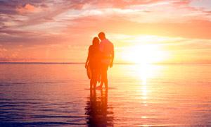 夕阳下沙滩约会的情侣摄影图片
