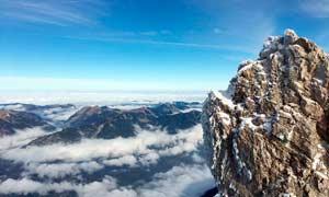 积雪岩石下的远山景观摄影图片