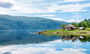 平静的湖边茅草屋摄影图片