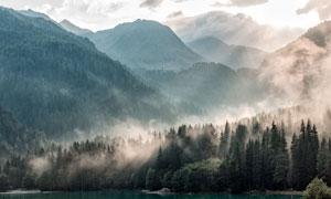 云霧繚繞的森林和湖泊攝影圖片