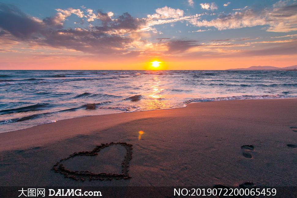 夕阳下的沙滩上的心形摄影图片