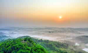 綠色大山山頂美麗的日出攝影圖片